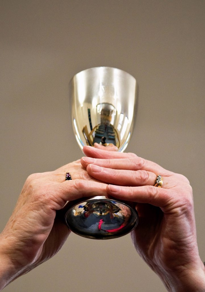 Stock Photo: 1889-72733 hands holding up a communion goblet, sheffield south yorkshire england