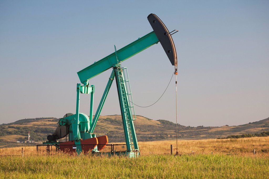 pumpjack in a field in the foothills at sunrise with blue sky, longview alberta canada : Stock Photo