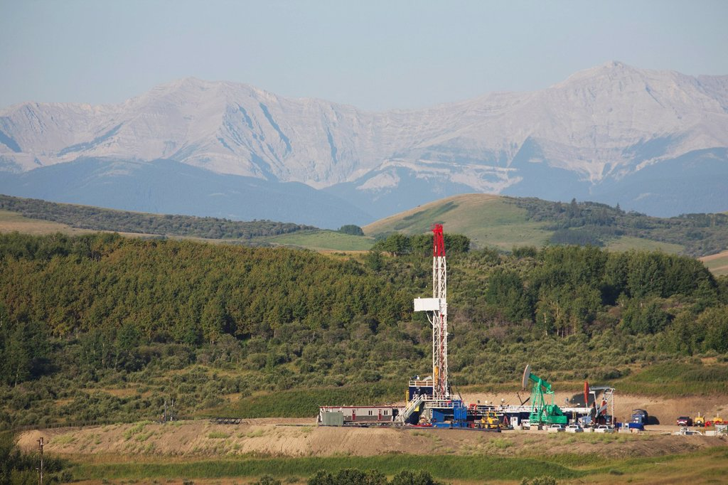 drilling rig with pumpjacks in the foothills with mountains in the distance and blue sky, longview alberta canada : Stock Photo