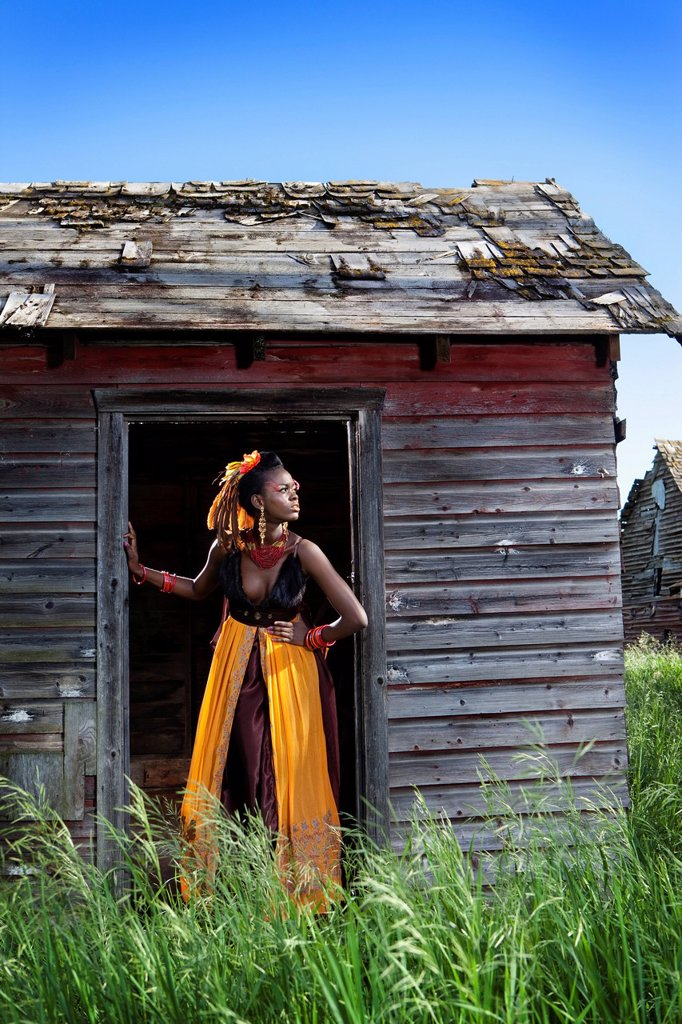 a young woman in a colourful dress, makeup and accessories standing in the doorway of a weathered shed, leduc, alberta, canada : Stock Photo