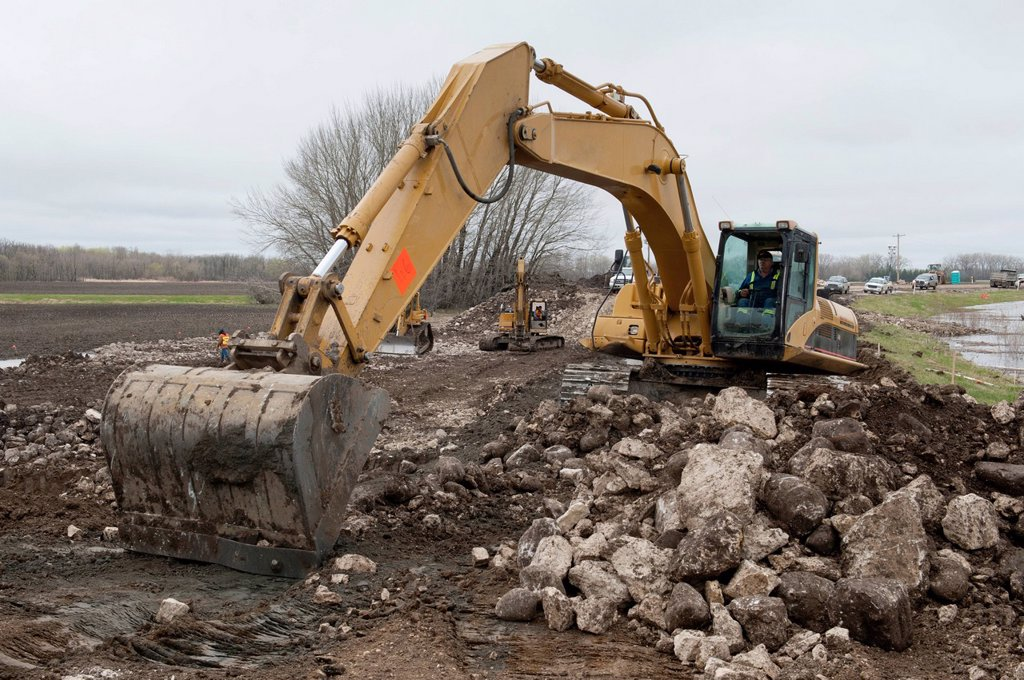 a tractor moves rock to form a barrier to prevent flooding, newton manitoba canada : Stock Photo