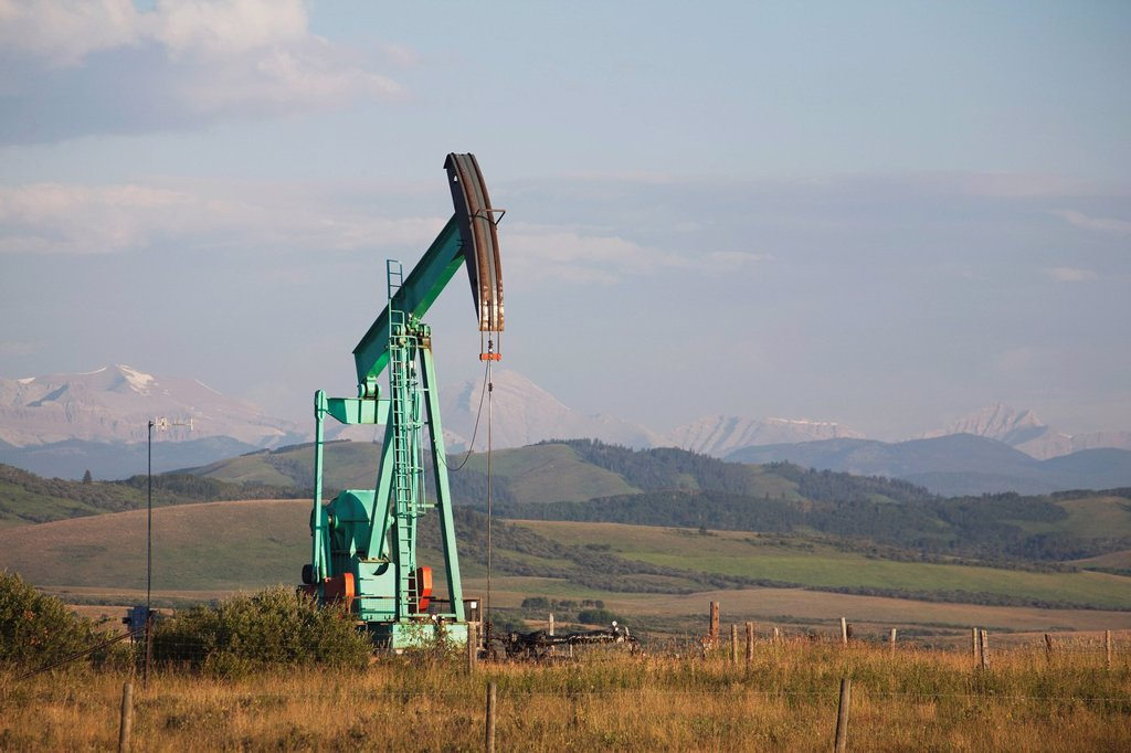 pumpjack in a field in the foothills with mountains in the distance at sunrise, longview alberta canada : Stock Photo