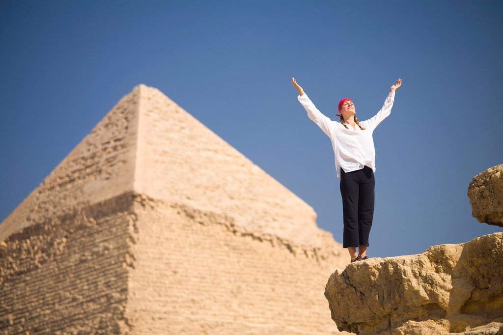 Stock Photo: 1889-74664 A Woman Tourist Raises Her Arms In Front Of The Pyramids Of Giza Near Cairo, Giza Egypt