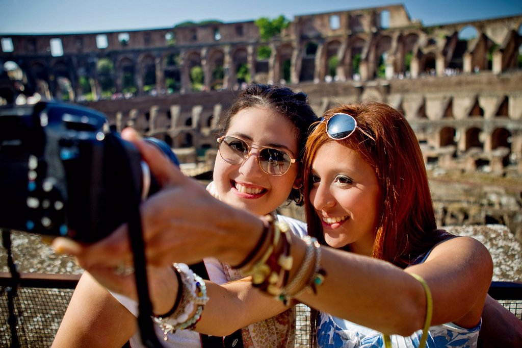 Two Young Women Take A Picture Of Themselves With A Camera And The Colosseum In The Background, Rome Italy : Stock Photo