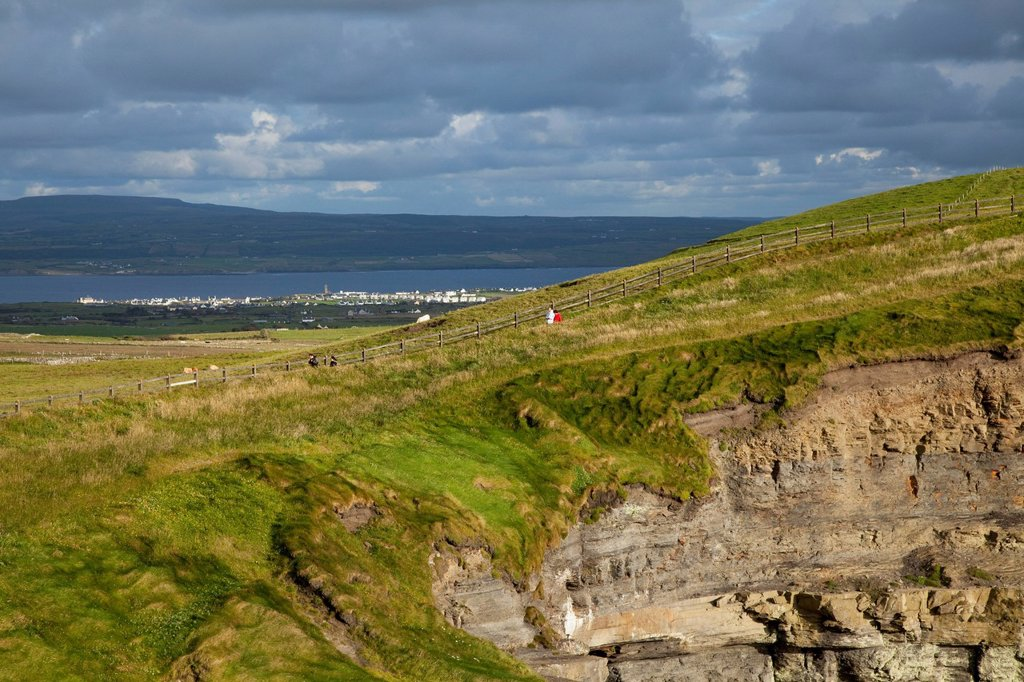 People walking along the grass at the cliffs of moher, county clare ireland : Stock Photo