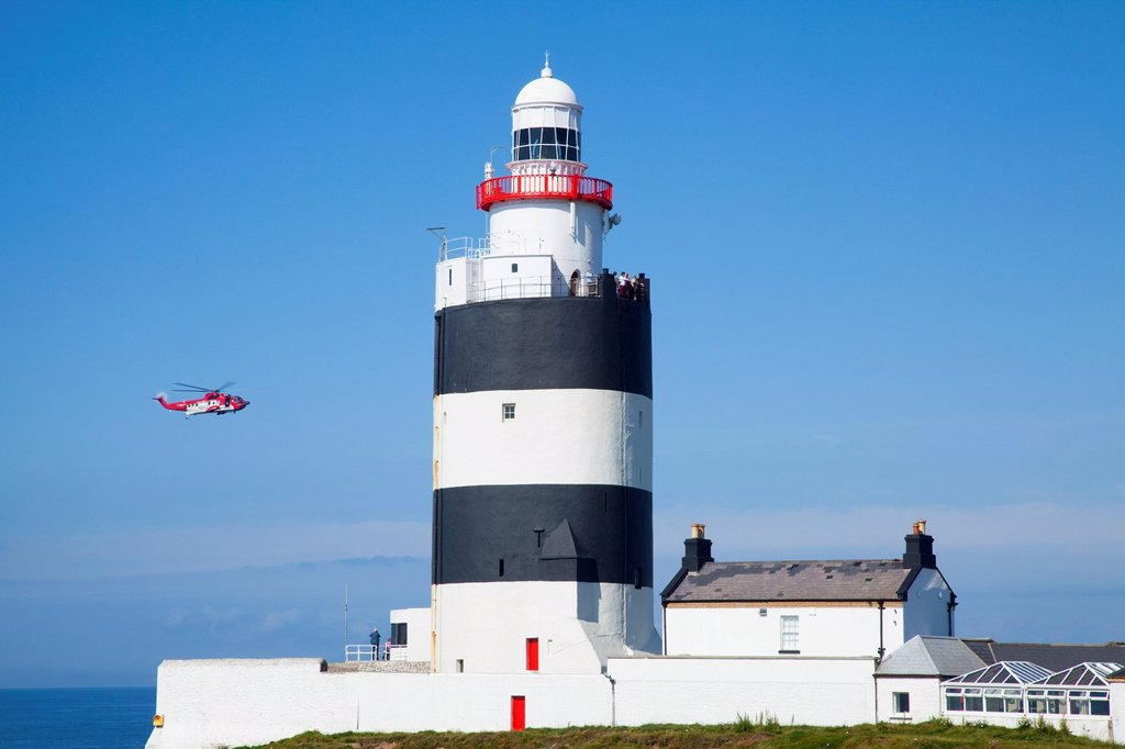 Stock Photo: 1889-75722 A helicopter flies by hook lighthouse, county wexford ireland