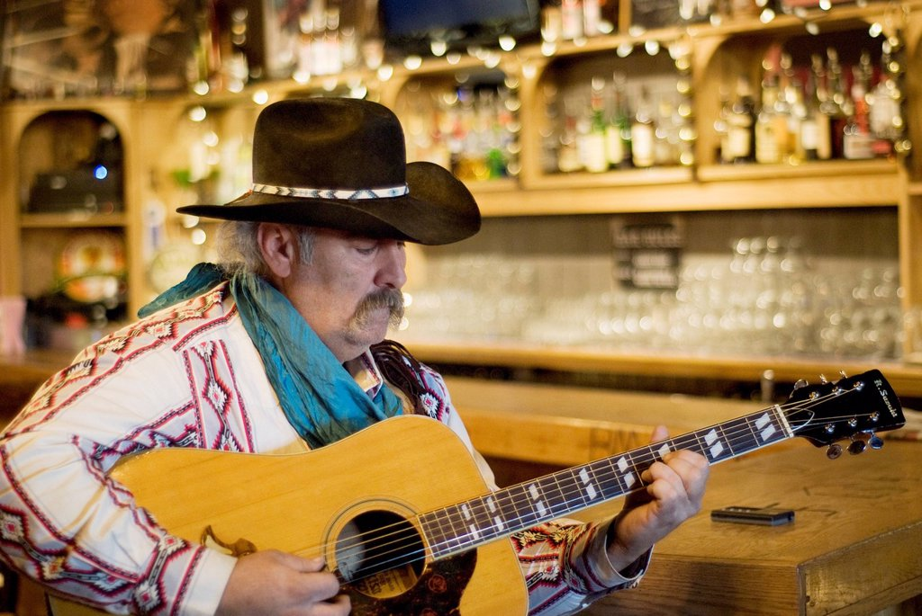 Stock Photo: 1889-76287 Cowboy playing guitar in a saloon, bragg creek alberta canada