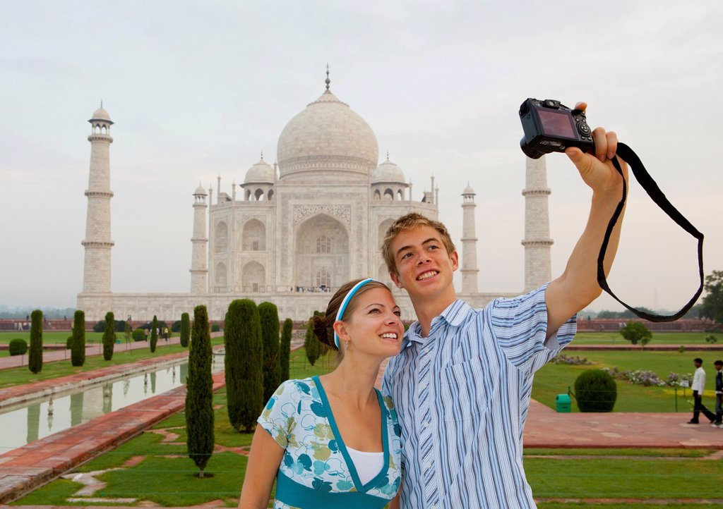 Stock Photo: 1889-76332 A young man and woman photograph themselves with the taj mahal in the background, agra uttar pradesh india