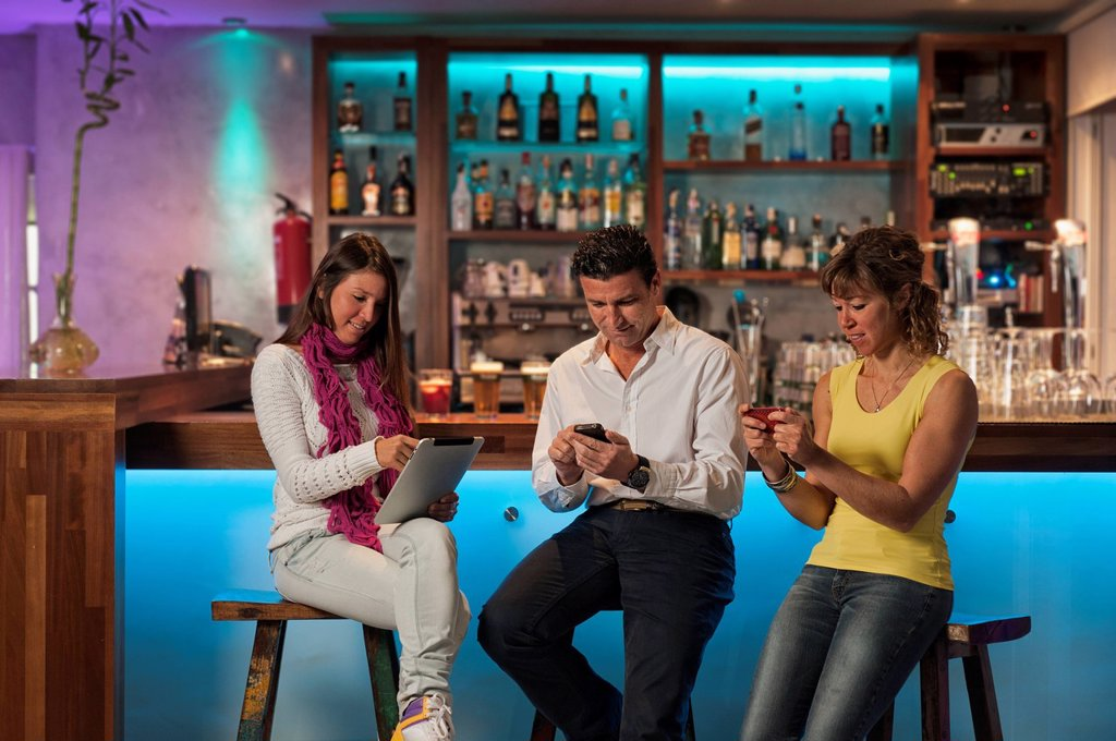 Stock Photo: 1889-76498 Three people sitting at the bar in republica cafe using their technology, tarifa cadiz andalusia spain