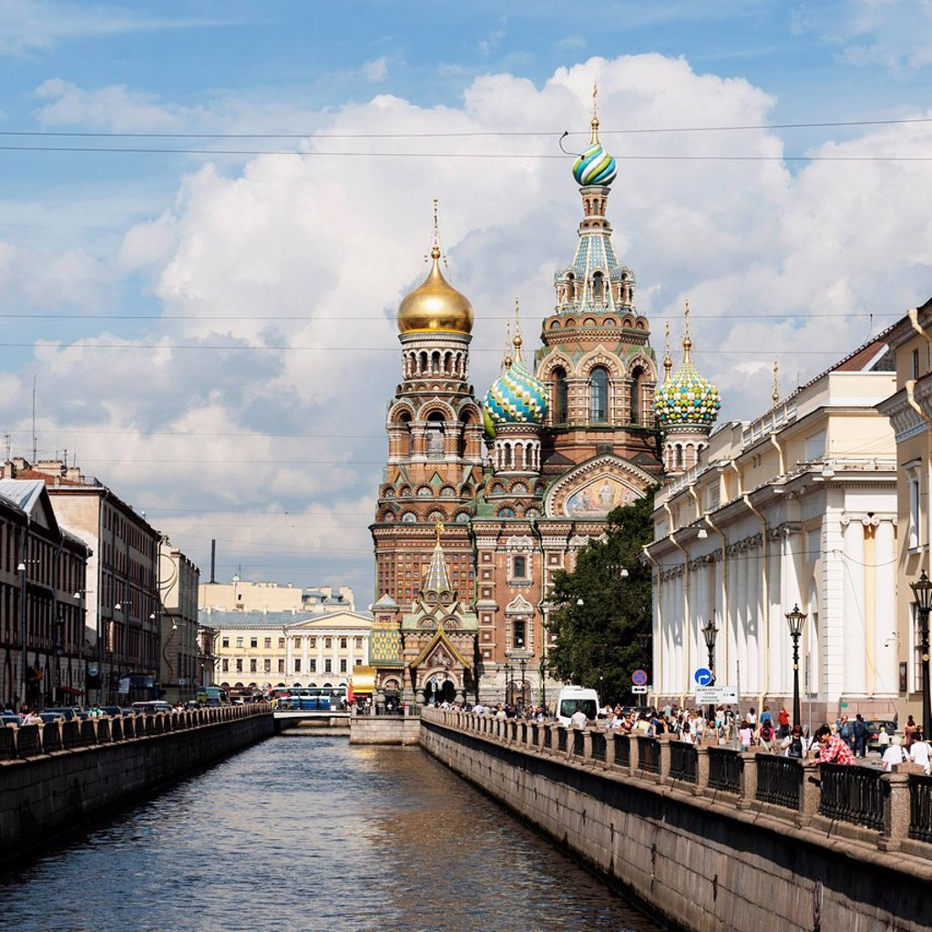 Stock Photo: 1889-76695 Pedestrians on the promenade along the griboedova canal with church of the savior on spilled blood in the distance, st. petersburg russia