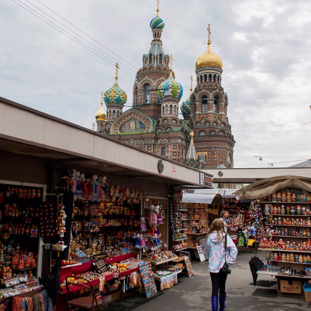Stock Photo: 1889-76701 A young woman walks through a market area with the church of the savior on spilled blood in the background, st. petersburg russia