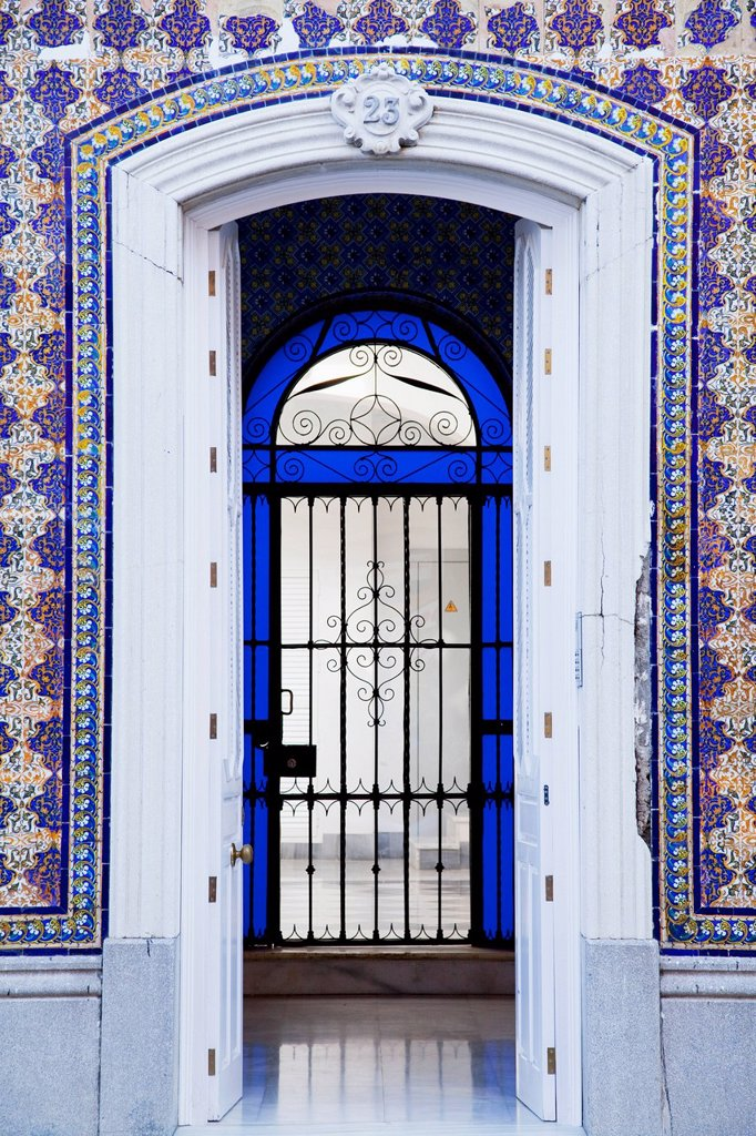 An open doorway on a building with ornate facade leading into a room with a gate surrounded by blue glass, chiclana de la frontera andalusia spain : Stock Photo