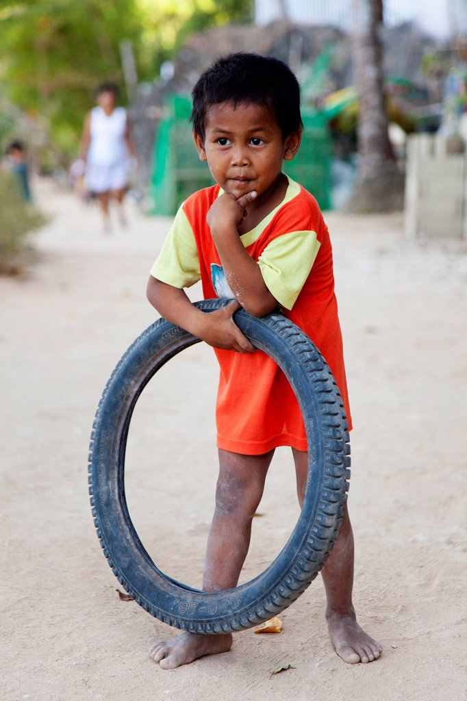 Stock Photo: 1889-76953 A Young Boy With His Toy Tire, El Nido Bacuit Archipelago Palawan Philippines