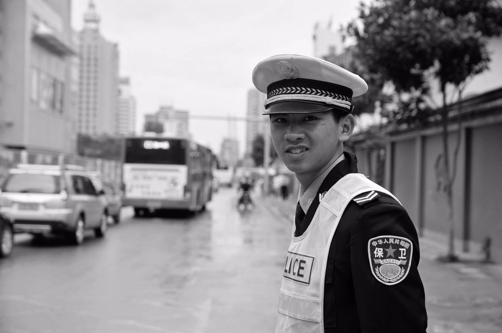 a young policeman standing on the side of a street, ruili yunnan china : Stock Photo