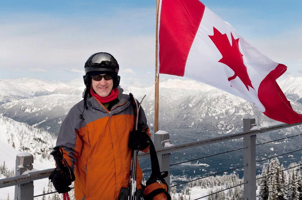 Stock Photo: 1889-79808 a skier stands beside the canadian flag on a balcony at a ski resort, whistler british columbia canada