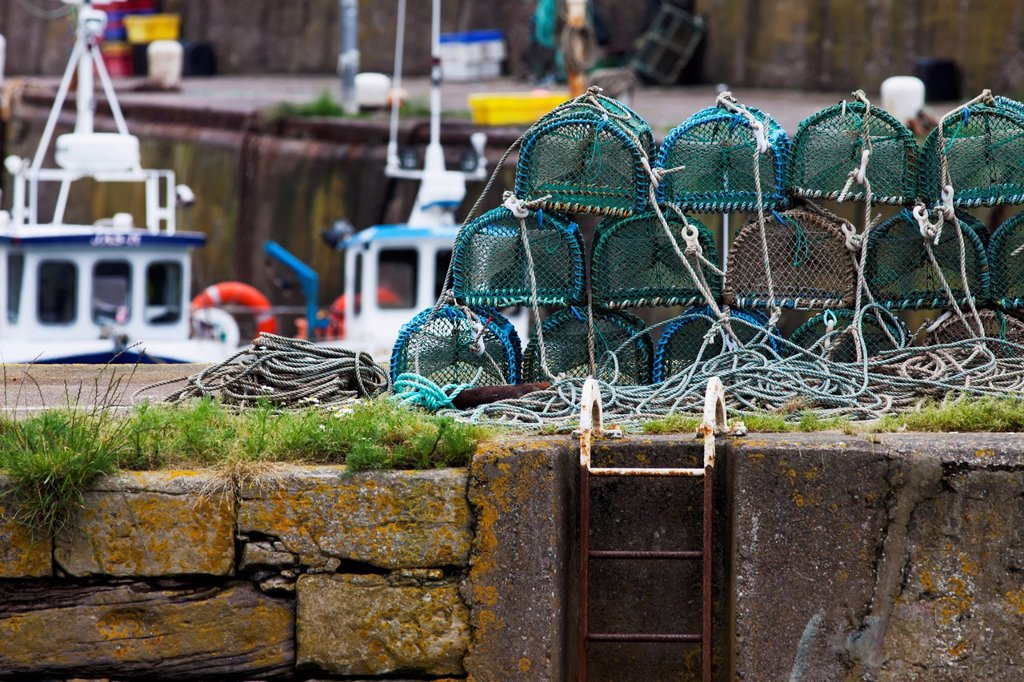 Crab traps piled on the shore at the harbour, burnmouth scottish borders scotland : Stock Photo