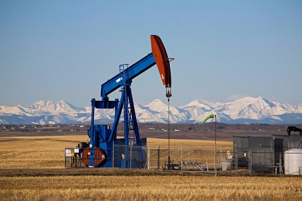 Stock Photo: 1889-82653 Pumpjack in a field with snow covered mountains and blue sky in the background, alberta, canada