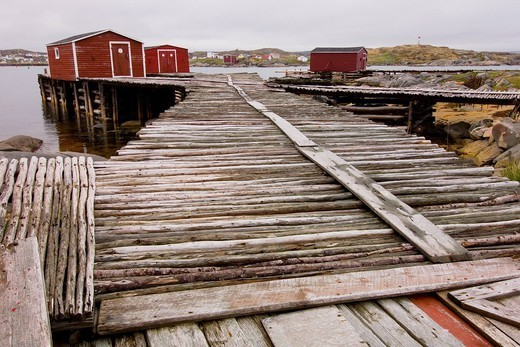 Red fishing huts at the end of a weathered wooden dock, tilting, newfoundland, canada : Stock Photo