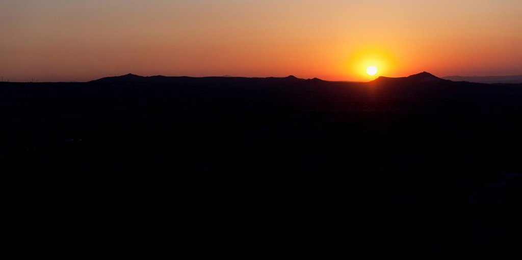 Stock Photo: 1889-83896 Silhouette Of The Landscape And An Orange Horizon With A Glowing Sun At Sunset, Aktepe Nevsehir Turkey