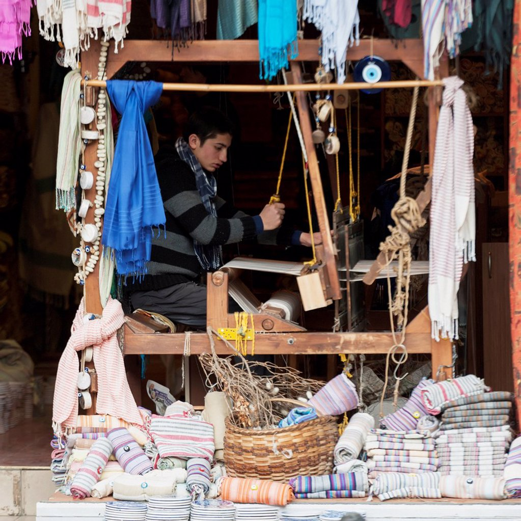 Stock Photo: 1889-84224 A Young Man Works A Loom In A Shop With Displays Of Fabric Out Front, Istanbul Turkey