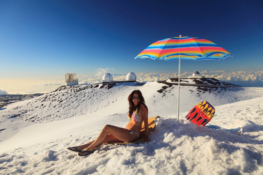Stock Photo: 1889-84517 A Woman In Bikini Sitting In The Snow With Beach Umbrella With The View From Mauna Kea Observatories, Mauna Kea Hawaii United States Of America