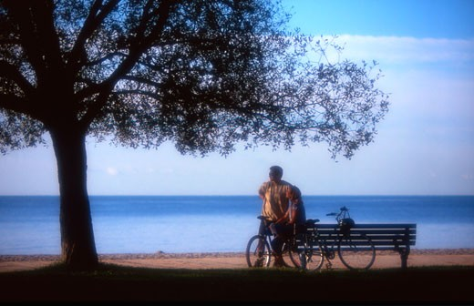 Stock Photo: 1889R-10217 Young Couple Bicycles on the Boardwalk