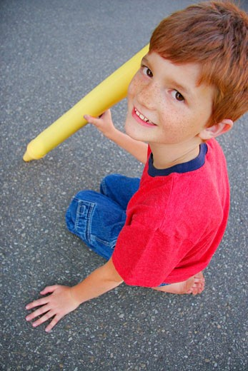 A close-up of a child sitting on asphalt with an oversized yellow crayon. : Stock Photo