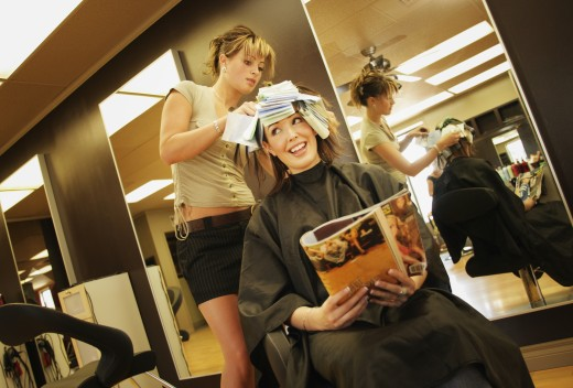 A young woman having her hair highlighted : Stock Photo