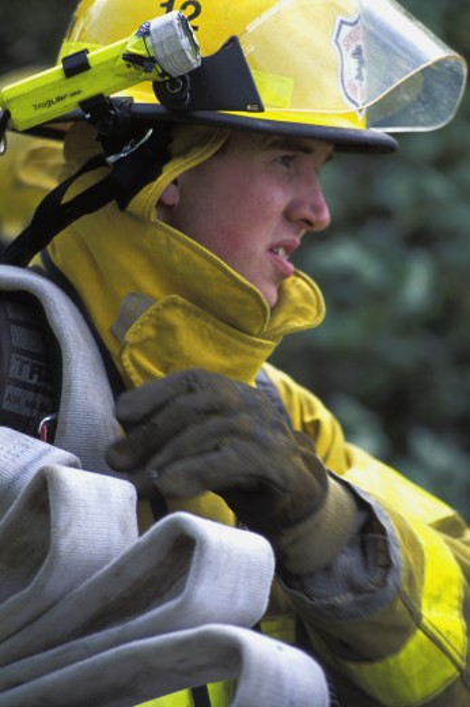 Fireman carrying empty hose : Stock Photo