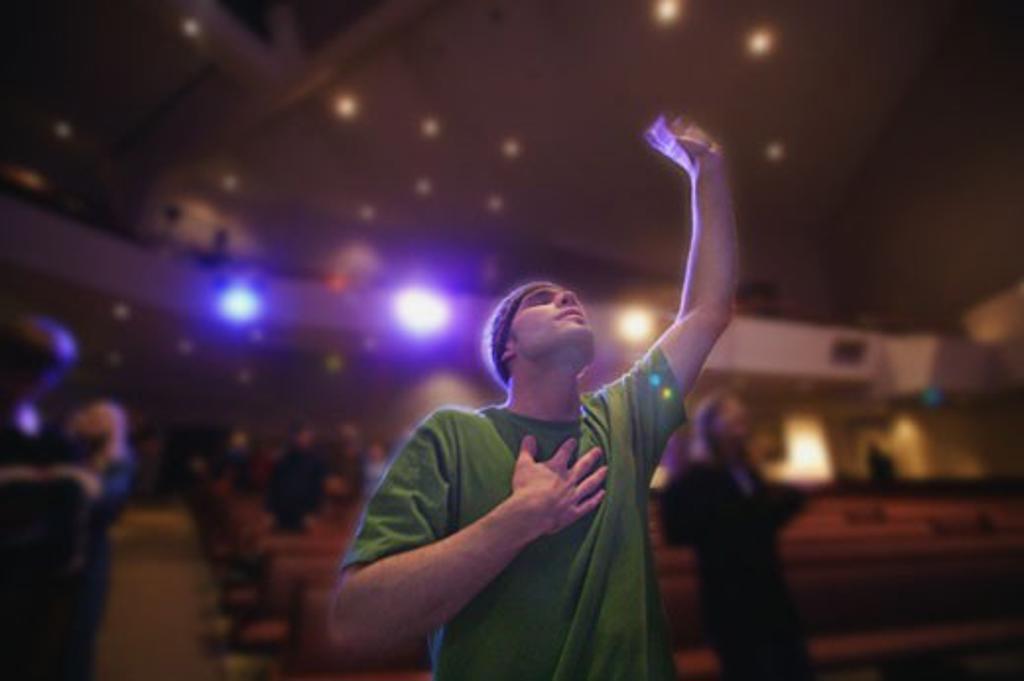Man raising hand in worship : Stock Photo