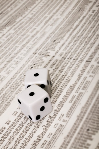 Dice on the stock market section of a newspaper : Stock Photo