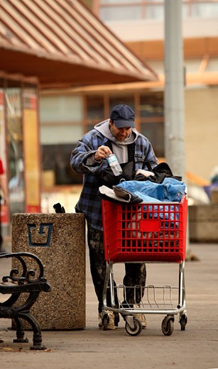 Stock Photo: 1889R-12708 Homeless man picking through the garbage