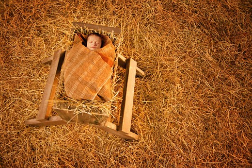 Baby Jesus lying in a manger : Stock Photo