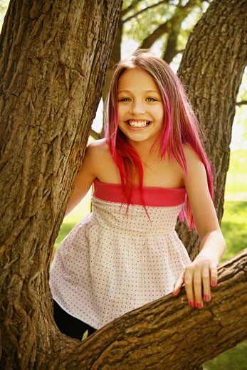 Girl in a tree; Girl with pink hair : Stock Photo