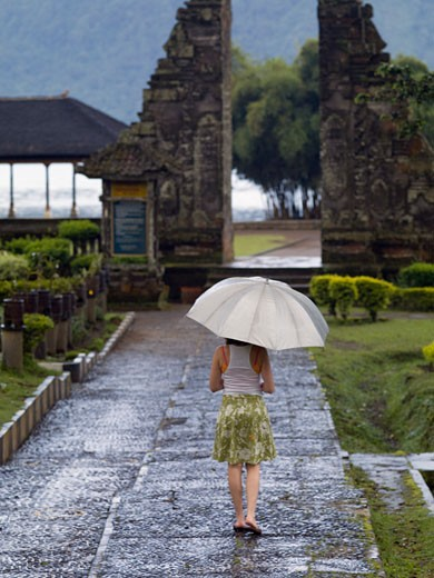 Ulun Danu Bratan Temple, Bali, Indonesia; Woman walking with umbrella : Stock Photo