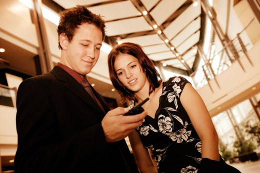 Stock Photo: 1889R-1806 Professional couple looking at cell phone