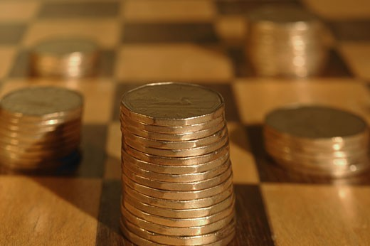 Piles of coins on checkerboard : Stock Photo