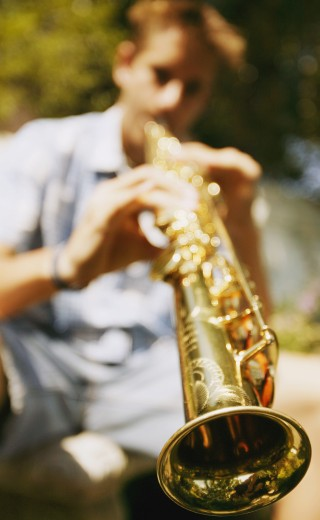 Young man plays soprano saxophone : Stock Photo