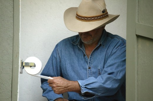 Stock Photo: 1889R-20051 Cowboy in the outhouse