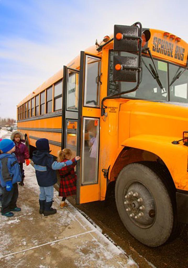 Stock Photo: 1889R-20622 Elementary schoolchildren boarding school bus on a winter day in Edmonton Alberta Canada
