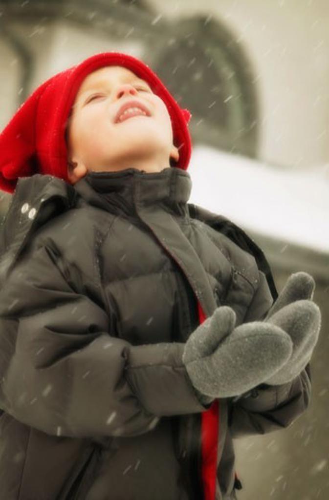 Stock Photo: 1889R-20794 Child enjoys catching snowflakes