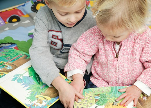Two children read a book : Stock Photo