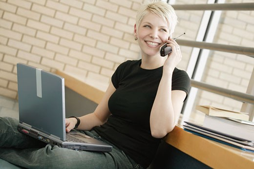 Student with cell phone and lap top computer : Stock Photo