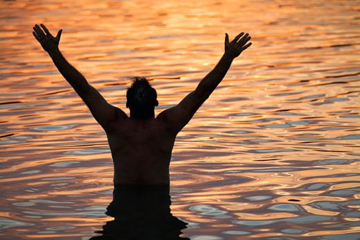 Man with arms raised in water : Stock Photo