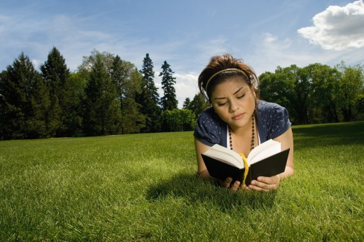 Portrait of young woman reading a book : Stock Photo
