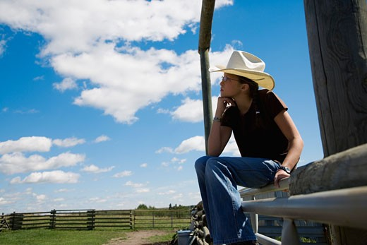 Stock Photo: 1889R-24997 Cowgirl sitting on gate