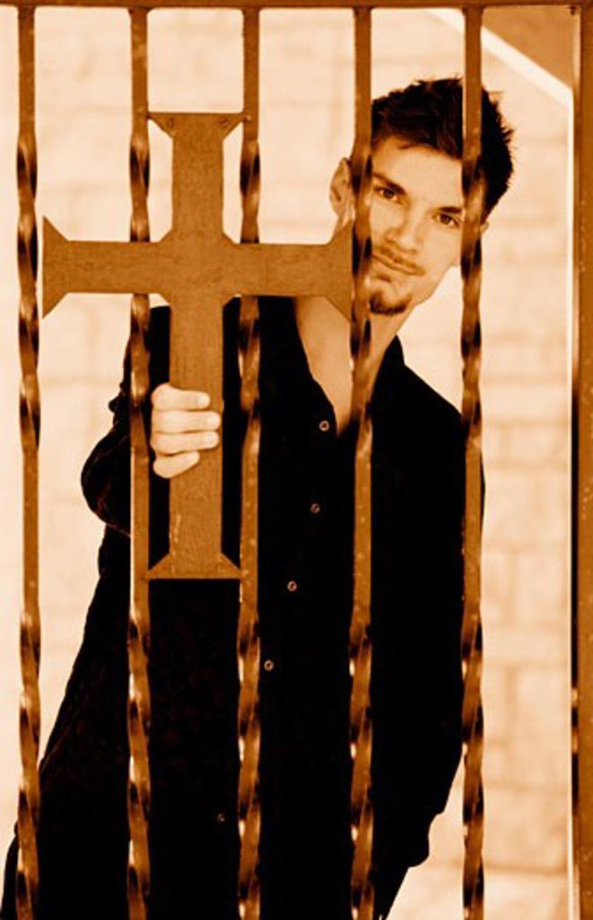 Man holding cross on iron fence : Stock Photo