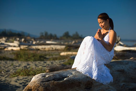 A young woman praying on the beach : Stock Photo
