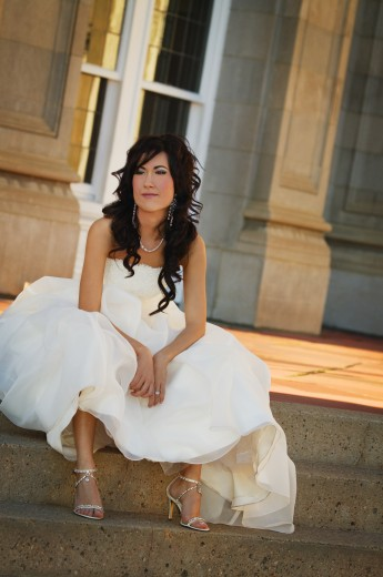 Bride sitting on outside steps in gown : Stock Photo