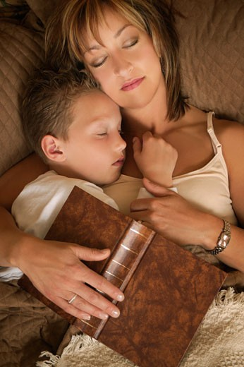 Stock Photo: 1889R-30125 Mother and son asleep after reading on a bed with book over them